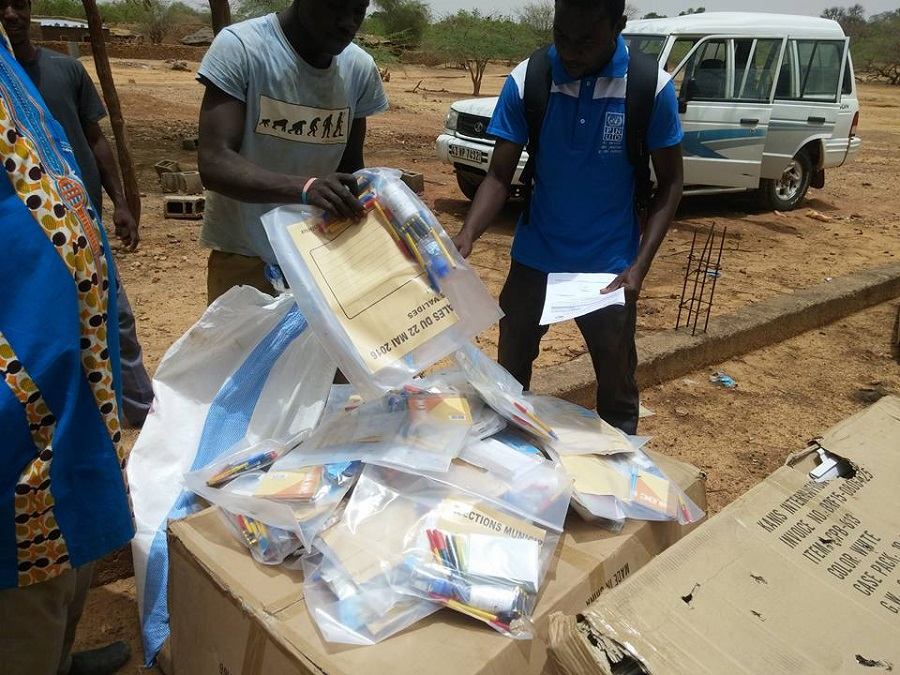 UN Volunteer Ferdinand Koanari (right) inspects electoral supplies delivered for the elections in Sebba, Burkina Faso.