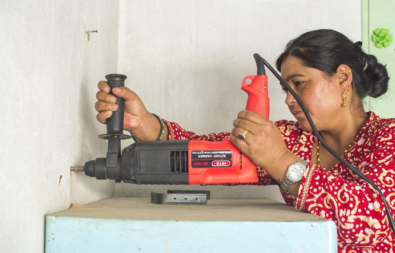 Una mujer protegiendo su propia casa contra los terremotos en Nepal.