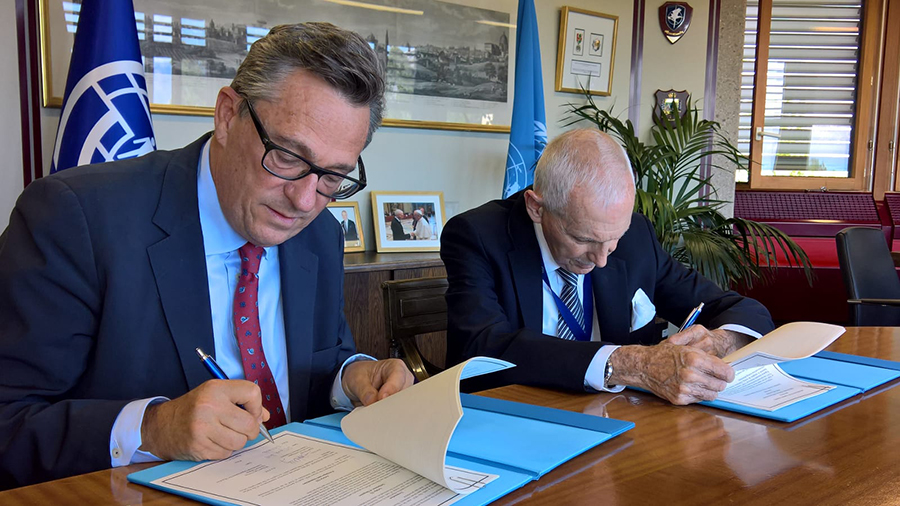 IOM Director General Ambassador William L. Swing (right) and UNV Executive Coordinator Olivier Adam sign a Memorandum of Understanding.