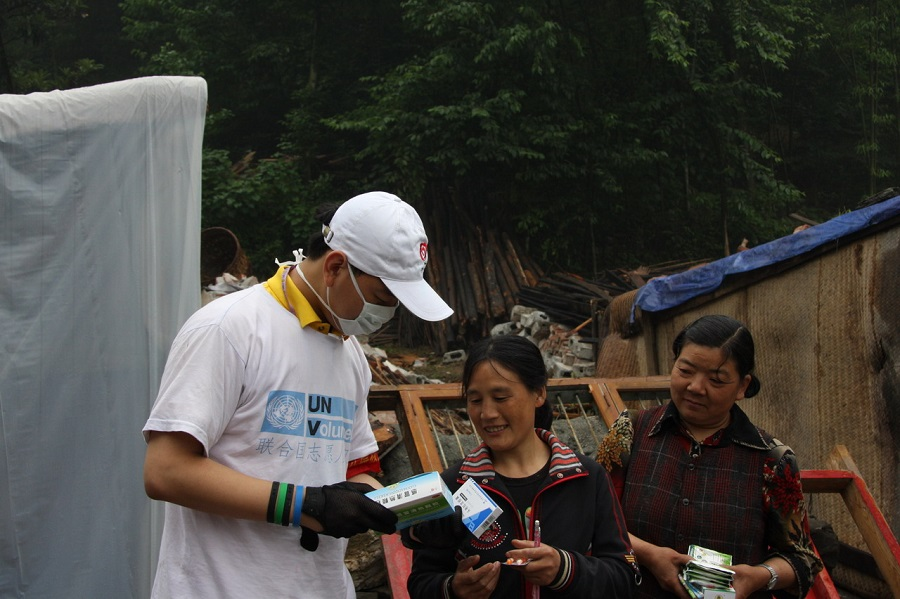 National UN Volunteer Gao Wei distributes food and medicine to local residents after Wenchuan Earthquake