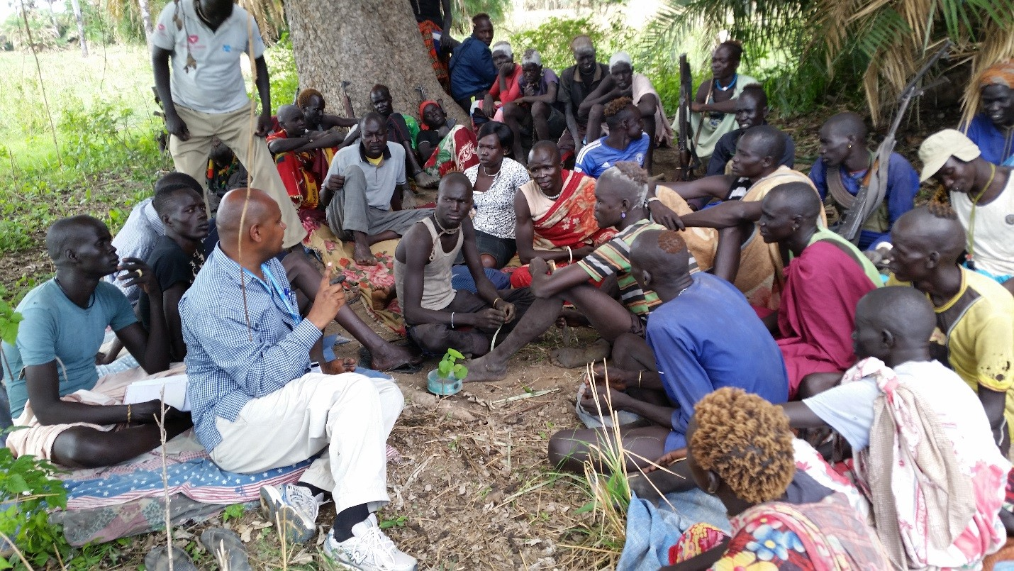 UN Volunteer Pastoralist Literacy and Education Specialist Solomon Bekele (centre) serves with UNESCO in Juba, South Sudan.  Here, he leads a discussion meeting with community members on the benefits of education at Aliet/Warabyie cattle camp.