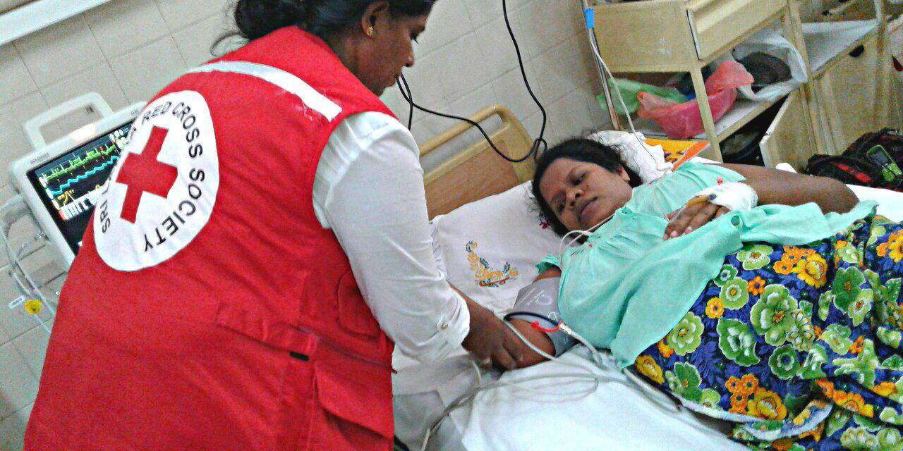 Un volontaire de la Croix-Rouge au chevet d'un patient dans un hôpital sri lankais (2017).