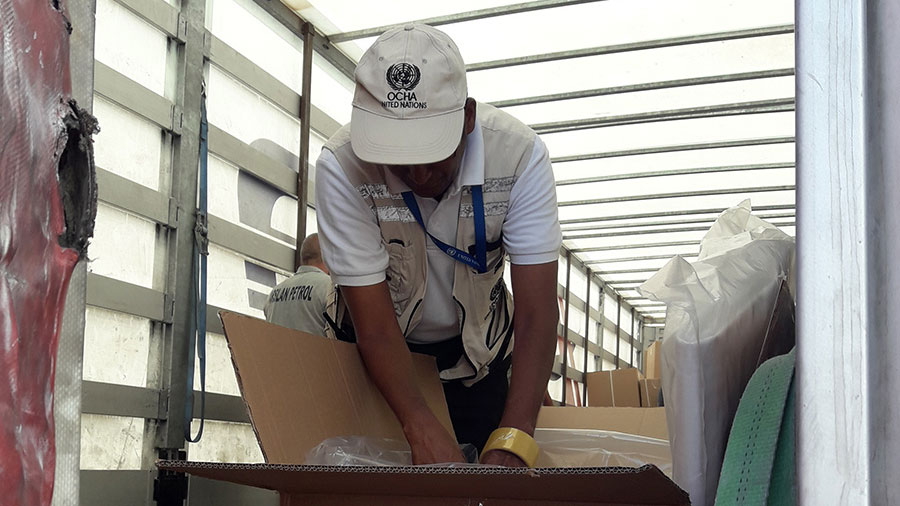 Thevanathan Nadesapillai, UN Volunteer with the United Nations Monitoring Mechanism for Syria (UNMM), checking the contents of a shipment of the International Organization for Migration (IOM) in Turkey.