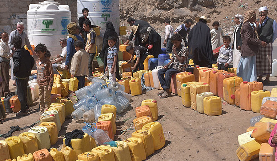 Families line up for water distribution in Yemen.