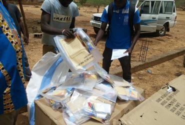 UN Volunteer Ferdinand Koanari (right) inspects electoral supplies delivered for the elections in Sebba, Burkina Faso.