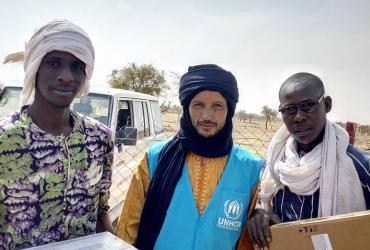 UN Volunteer UNHCR Oussamata Iba (centre), with two fellow refugees from the camp of Goudebou, Dori, Burkina Faso.