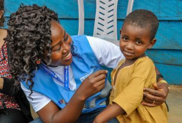 Marriane Enow Tabi, UN Volunteer Monitoring Assistant with the World Food Programme in Meiganga, Cameroon, with a child from the Lolo refugee site.