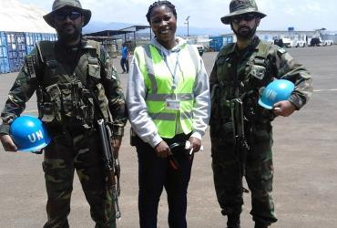 Aya Alice Kouakou (Côte d'Ivore) UN Volunteer Air Operations Assistant, with UN peacekeepers on the tarmac of Bukavu, Democratic Republic of Congo.