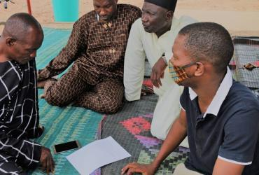 Mamadou Bah (right), national UN Volunteer Community Change Management Specialist with UNICEF, speaks to the Village Development Committee of Nafugan In Upper River Region of The Gambia on the feedback mechanism.