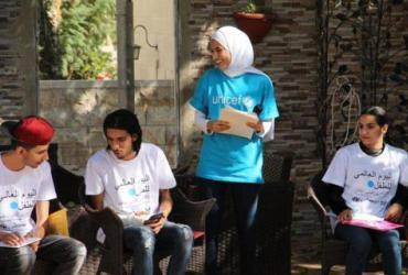 UN Volunteer Haya Al-Jamal (standing), participating in an event for World Children's Day in Jordan.