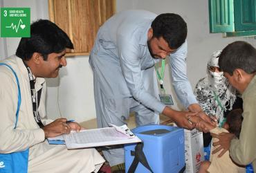 Husnain Haider Baloch, national UN Volunteer, talking to a beneficiary of the measles vaccination campaign in Dera Ghazi Khan, Punjab, Pakistan.