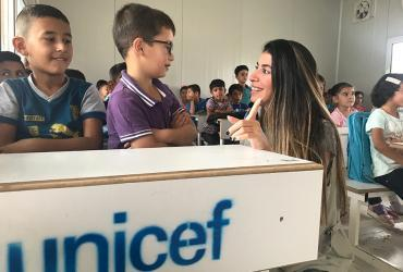 Rasha Abou Dargham with Syrian refugee children in a UNICEF-supported classroom in Baharka Camp, Iraq.