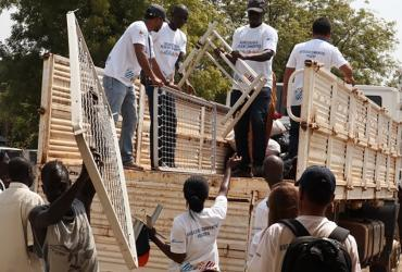 Gideon Sackitey (right) helps colleagues to offload mattresses - part of the items they donated to the children's ward at Bor Town Hospital  in South Sudan - from a truck.