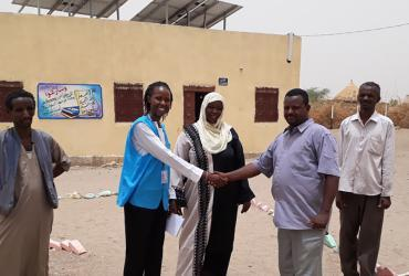 UN Volunteer Janet Simion (second from left) with beneficiaries near a solar-powered water pumping system in Girba refugee camp, eastern Sudan.