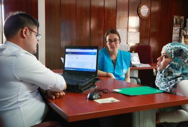 Cansu Güngör (centre), a national UN Volunteer, is supporting a beneficiary registration session at the Turkey's employment agency in Ankara.