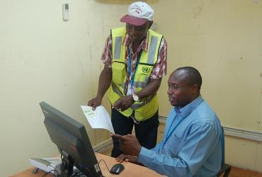 Patrick Ndalila (Kenya, standing), UN Volunteer Transport Dispatch Assistant with UNMIL, discusses work processes with a colleague in the mission.