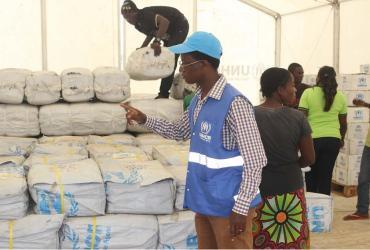 Kambarangwe inspects Core Relief Items in the Warehouse for distribution to refugees at Kenani transit centre in Nchelenge. Photo by UNHCR/Bruce Mulenga